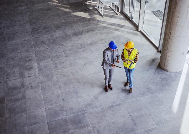 Dwóch pracowników analizujących plany budowy