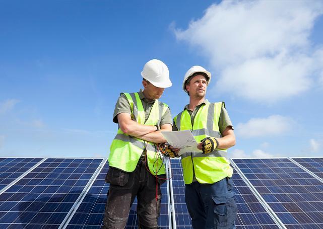 Dwóch pracowników stojących przed panelami słonecznymi